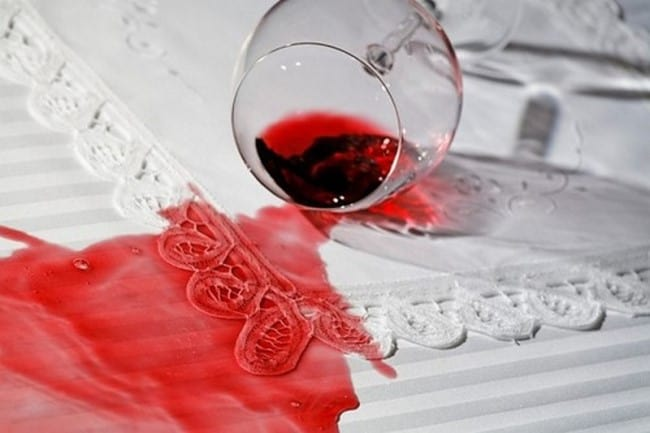 Разлитое красное вино на белой ткани