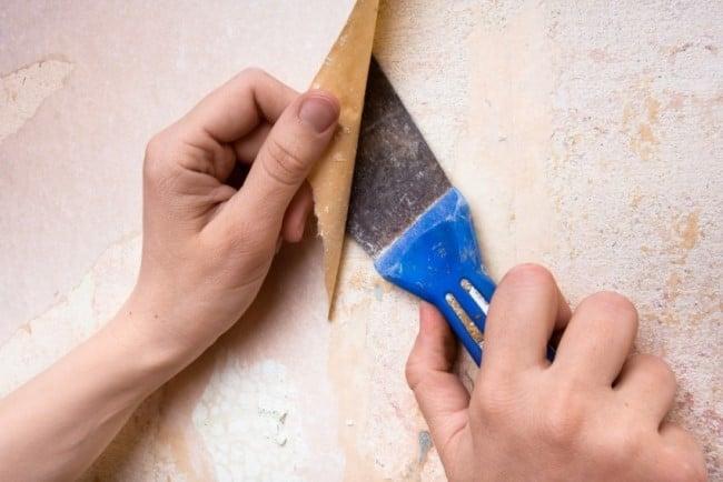 Оставшиеся на стенке небольшие фрагменты сдерите шпателем, наждачной бумагой или смочите повторно