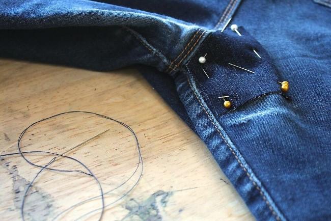 Вырежьте латку из старых джинс, приклейте с помощью клеевой ленты и прошейте ее по краям
