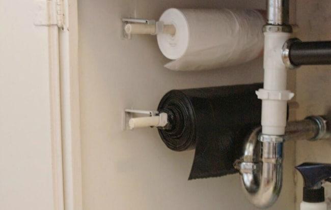 Для удобства многие домохозяйки устанавливают под мойкой простые держатели для туалетной бумаги, нанизывая на них рулон мусорных пакетов